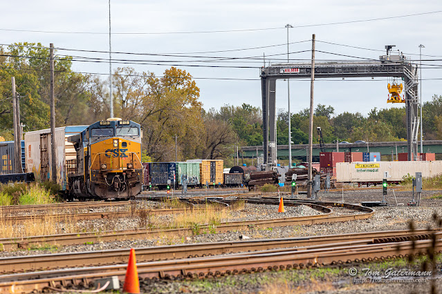 Q367-06 makes its way past a container crane