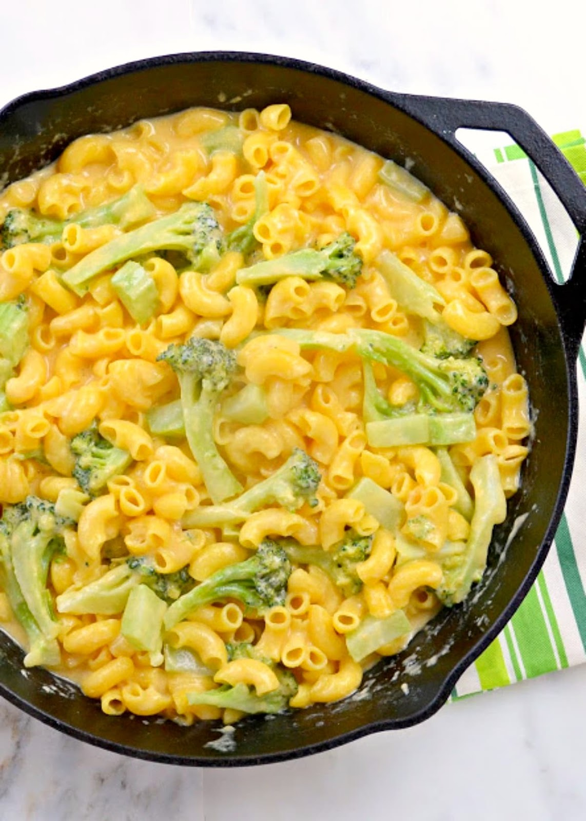 Creamy Macaroni and Cheese with Broccoli in a cast iron skillet with a green and white striped hand towel.