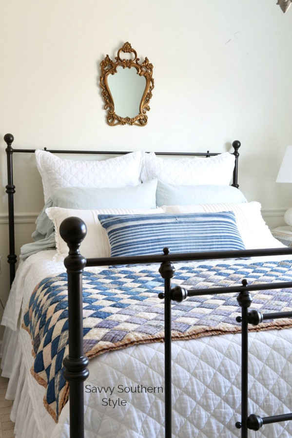 iron bed with blue and white bedding