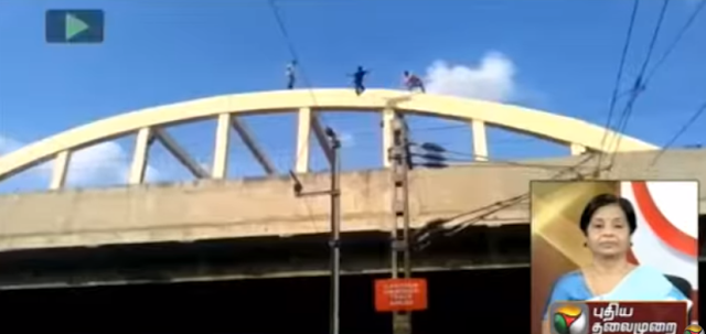 An unidentified young man jumped to his death from a bridge near railway station in Madurai on Thursday.  The shocking incident unfolded in full public and was caught on camera.  A video of the incident, which was telecast by Tamil news channels, shows the man on the arch of the bridge. Two onlookers also got on to the bridge to try to get him down.