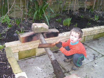 sawing an apple log up against brick raised flowerbed