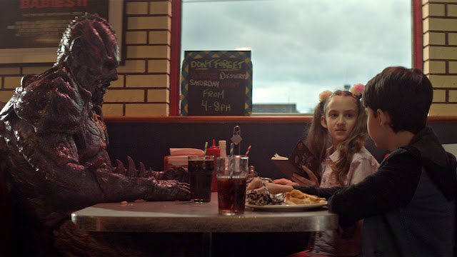 alien eating at a diner with kids
