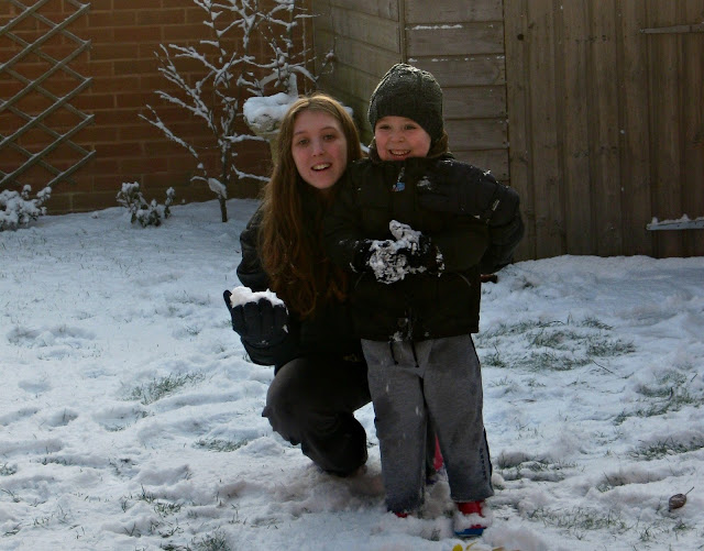 Small boy and older girl, posing in a snow covered garden.