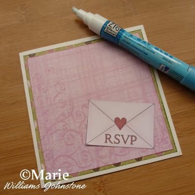 Using a zig glue pen to stick on a mini envelope embellishment