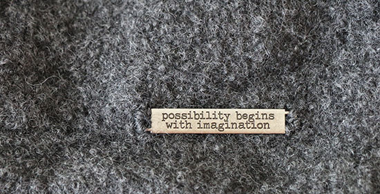 "Silver metal label that says ""possibility begins with imagination"" sewn onto dark gray wool felt fabric."