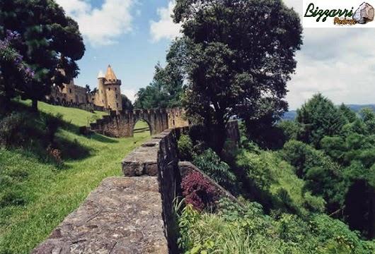 Vista do muro de arrimo com pedra do castelo de pedra e da torre de pedra no pico de uma montanha que da para ver o por do sol a 50 Km de distância.
