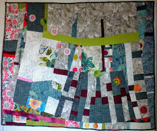 Improvisational quilt with marine blue shot cotton, red, pink, green, and white prints on a background of black, white, and red daisies.