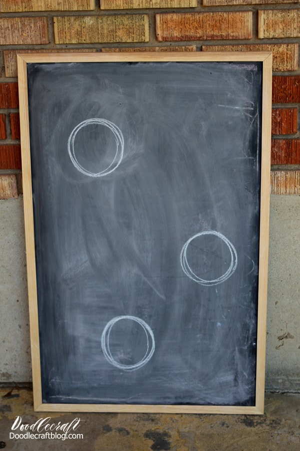 Circles drawn in chalk on an old chalkboard ready to upcycle into a bean bag toss game