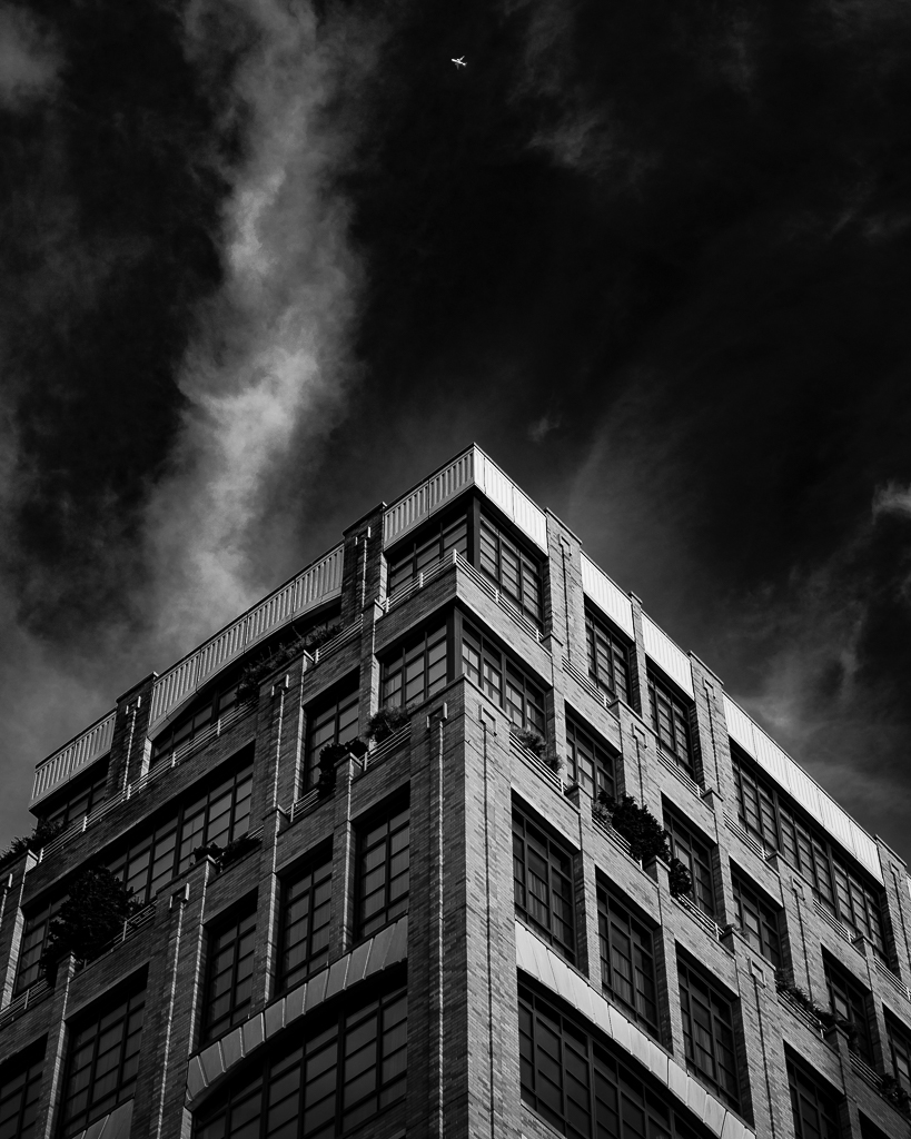 a black and white photo of a new york building with an airplane passing overhead