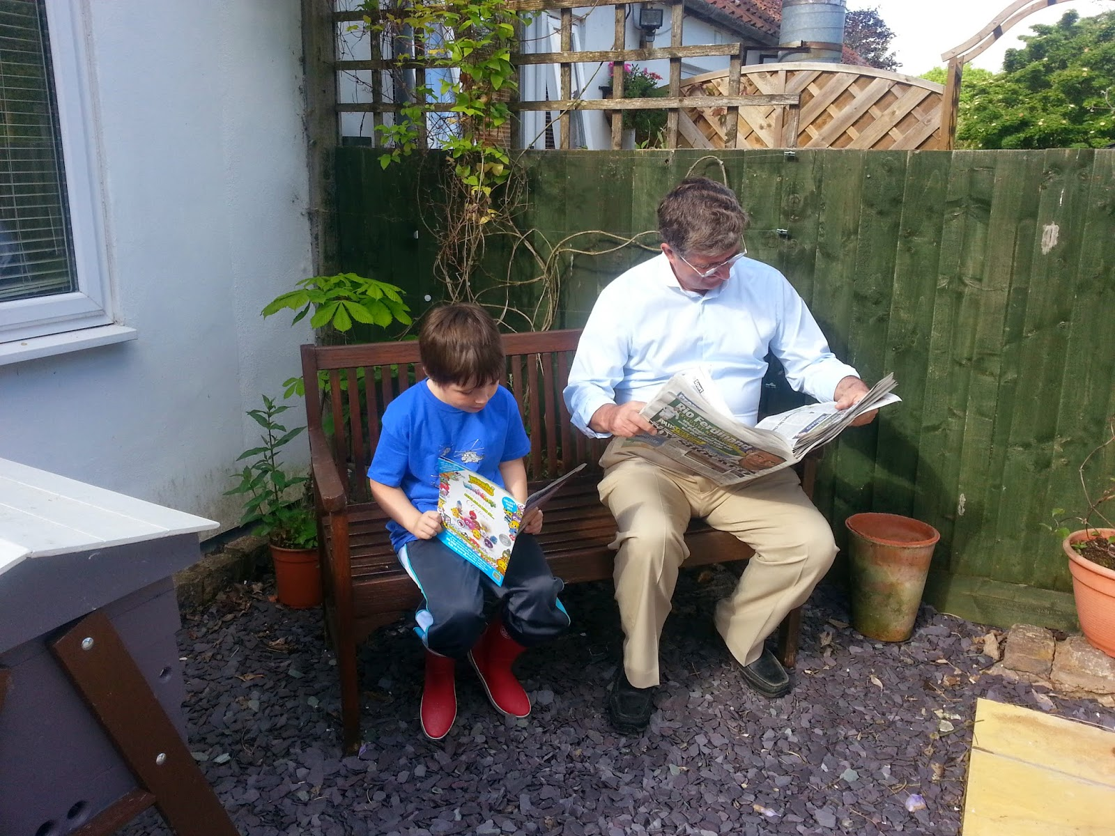 Grandfather and grandson reading newspapers side by side