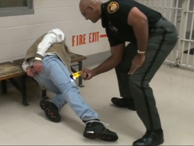 A guard at Franklin County Jail in Ohio presses a Taser gun into the leg of inmate in December 2009