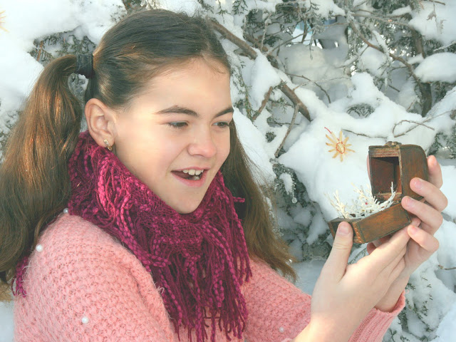 Smiling girl admiring snowflake jewelry inside a wooden jewelry box