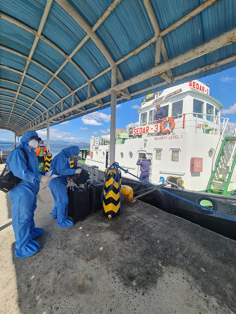 tugboat water taxi at Batangas port with waiting seafarers in full PPE