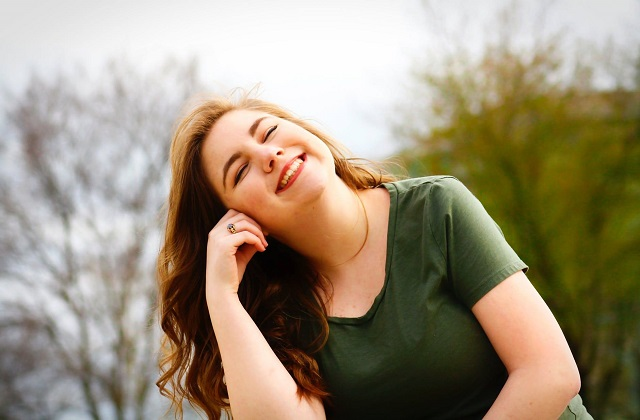 pretty woman smiling eyes closed in green shirt sunshine on face
