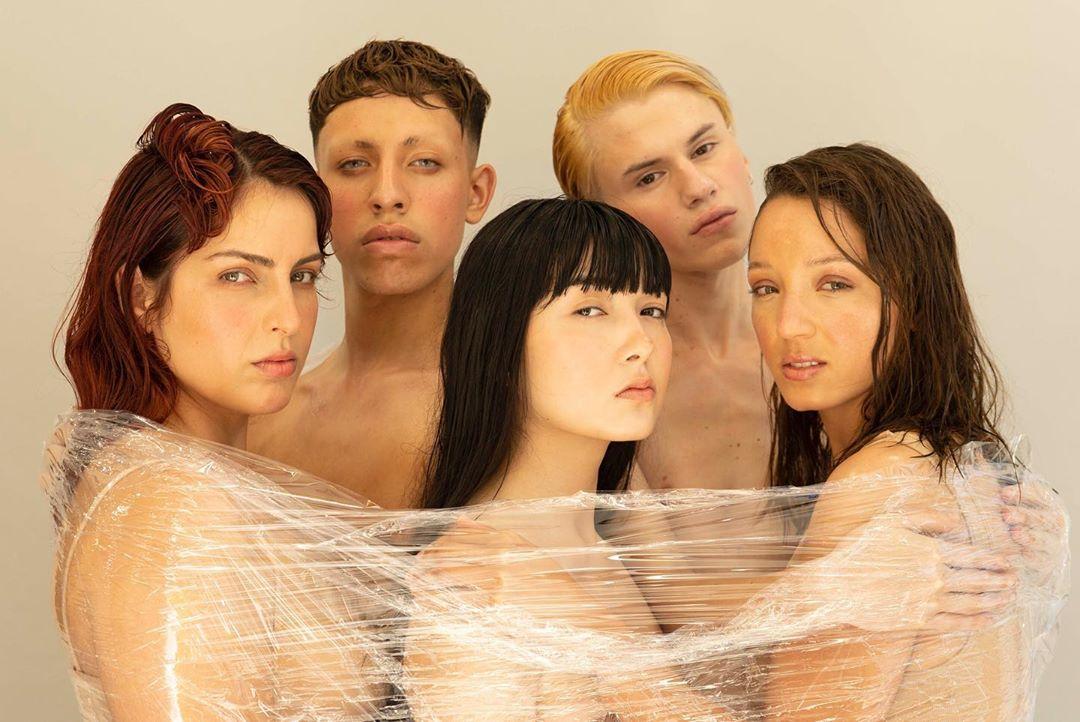 Grupo de personas jóvenes mira a la cara envueltos en plástico