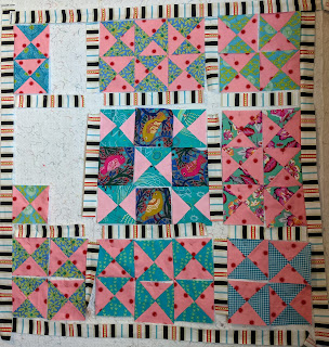 Testing the quilt center combining five hourglasses with four alternate blocks of printed bird fabric