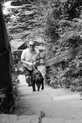 Monochrome photo of Neil and Liggy climbing a steep flight of stone steps.