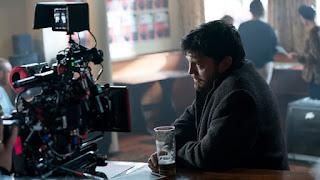 Tom Burke behind the scenes filming in a pub