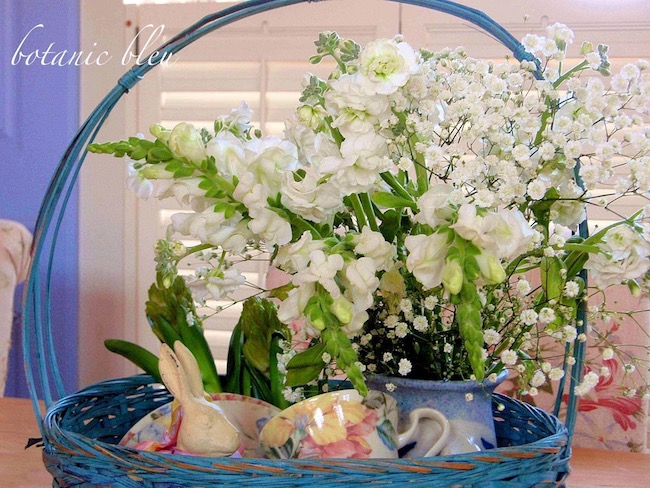 Beautiful Spring Centerpiece collects live flowers, faux flowers, colorful dishes, iron bunnies in a brilliant blue basket