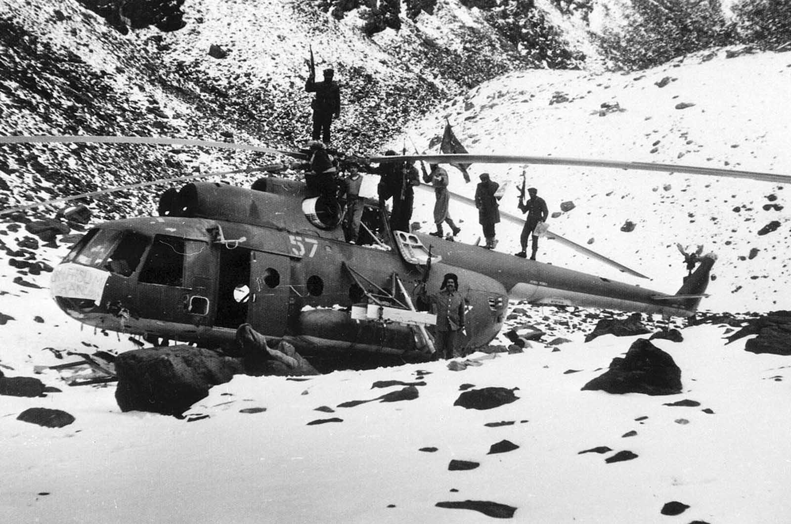 Afghan guerrillas atop a downed Soviet Mi-8 transport helicopter, near the Salang Highway, a vital supply route north from Kabul to the Soviet border, January 12, 1981.