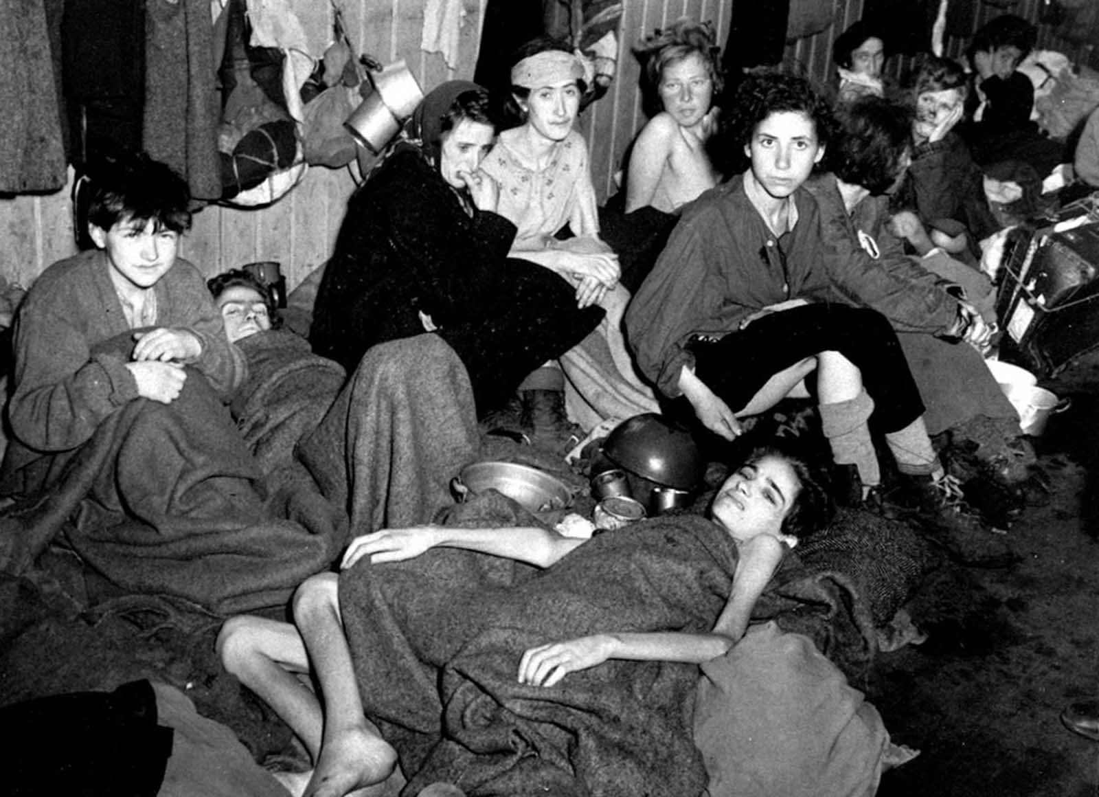 Women and children, some of over 40,000 concentration camp inmates liberated by the British, suffering from typhus, starvation and dysentery, huddle together in a barrack at Bergen-Belsen, Germany, in April 1945.