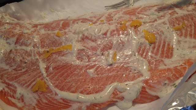 Close up of a filet of salmon with lemon rind slices and covered with white dill dip.
