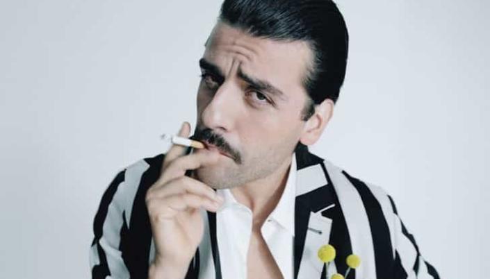 Imagem: Oscar Isaac em um ensaio fotográfico, na qual ele está vestido de Gomez Addams, uma camisa de botão branca com listras pretas, pequenas flores amarelas num bolso, cabelo preto penteado e liso, um bigode fino, olheiras pretas e fumando um cigarro.