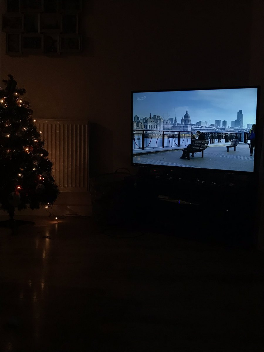Christmas tree with lights on and TV with Love Actually on