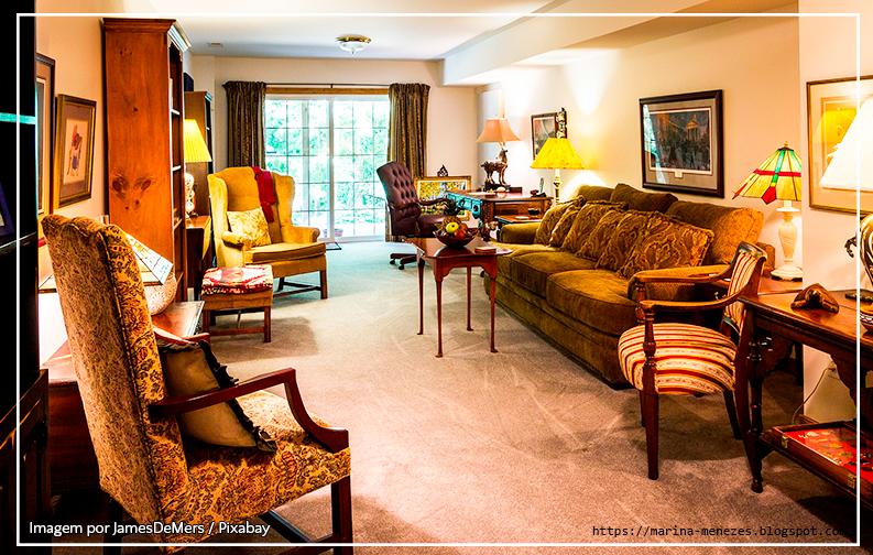 A imagem mostra uma sala de estar, com móveis clássicos de madeira. Nela, é possível ver uma poltrona e um sofá, que combinam entre si