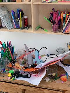 Rodet bord med limpistoler, krea grej og tegninger i en stor bunke.