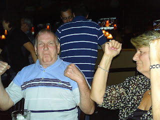 Tod and Paula sitting at a table with their hands in the air as if dancing.
