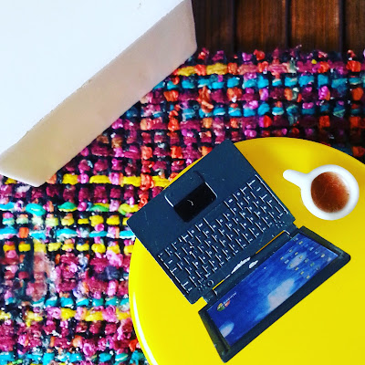 Aerial view of a one-twelfth scale modern miniature ottoman and coffee table with a laptop and a coffee on it.