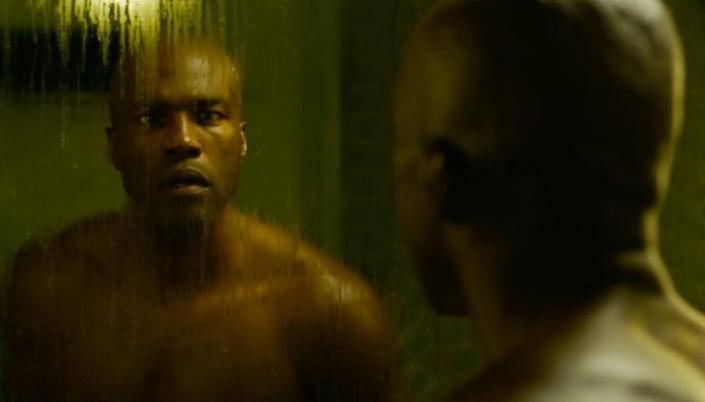 Imagem: o ator Yahya Abdul-Mateen, um homem negro e alto, careca e sem camisa, olhando para si mesmo num espelho molhado de um banheiro mal iluminado com uma expressão de dúvida.