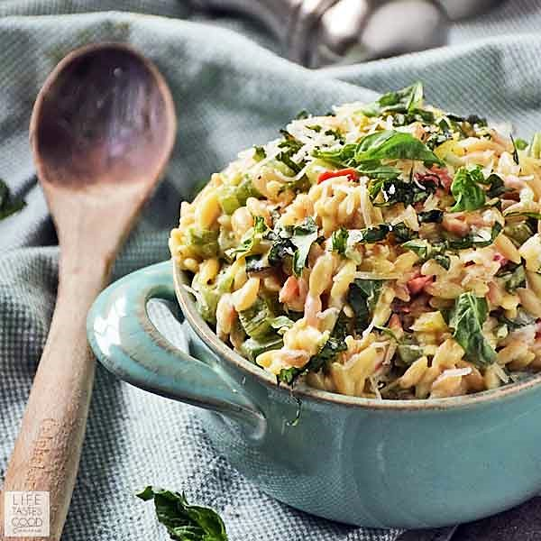 Garlic and Parmesan Orzo with fresh veggies in a blue serving dish ready to eat. A wooden spoon for serving sits on the left side of the blue dish