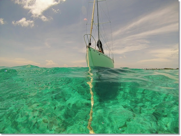 Sailboat anchored in clear turquoise water  of the Bahamas.