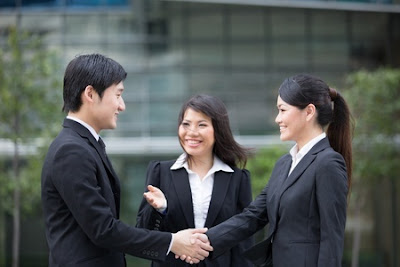 man and woman shaking hands as another woman looks on