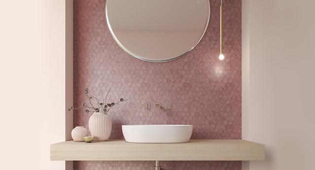 A millennial pink tile backsplash behind a mid-century modern vanity updates this bathroom.