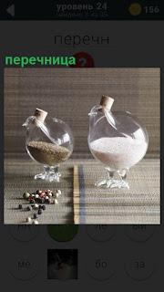 Нас столе стоят две перечницы в виде птиц с клювами, наполовину заполненные