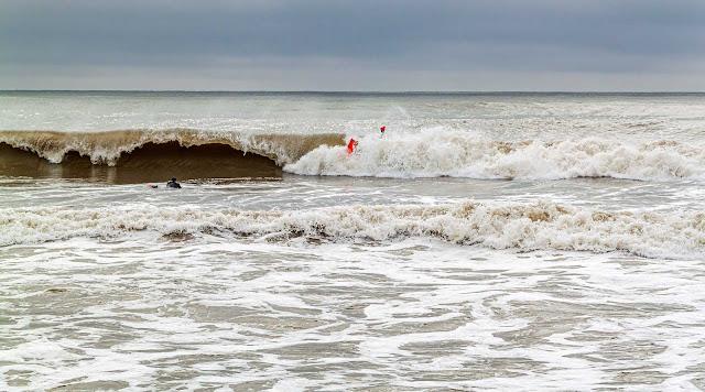 La ola forma una cueva en sus agua y nadadores sobre ella.