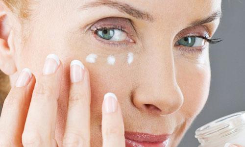 Mujer madurando aplicando crema antiarrugas en el contorno de ojos