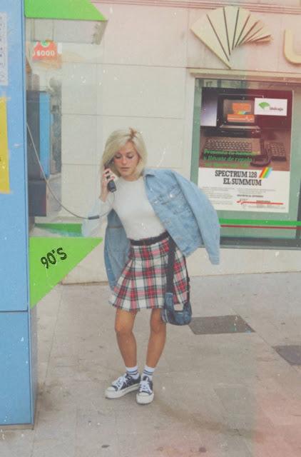 Estilo de los años 90 inspirado en Jennifer Aniston en Friends con suéter blanco, falda de tablas cuadros escoceses, zapatillas y calcetines blancos con raya negra en cabina telefónica