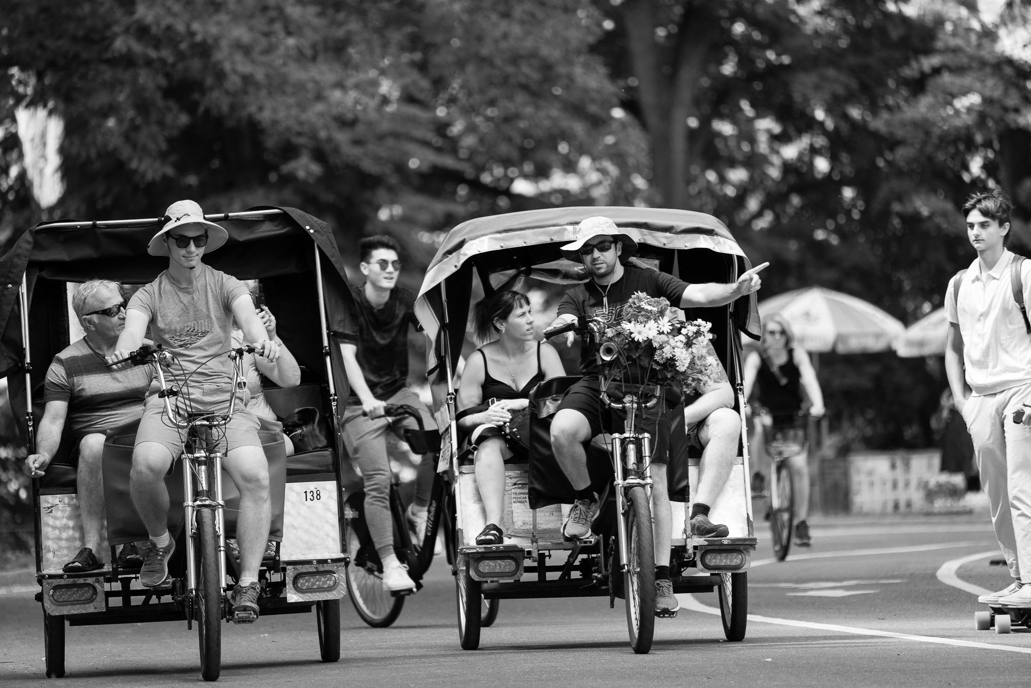 a black and white photograph of pedicabs and a skateboarder in central park new york