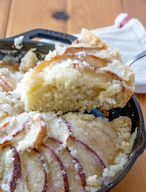 first slice of dutch apple cake being lifted out of cast iron skillet