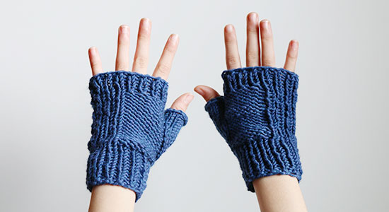 The backs of a child's hands wearing hand knit blue fingerless mitts on a white background.