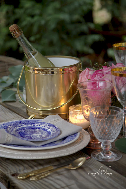 Blue and white dishes and a gold ice bucket on table