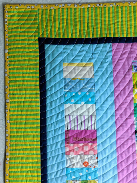 Concentric quarter circles are quilted starting at the top left corner of the quilt
