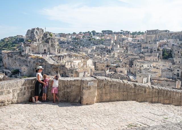 Mujer y dos niños con la ciudad de Matera al fondo