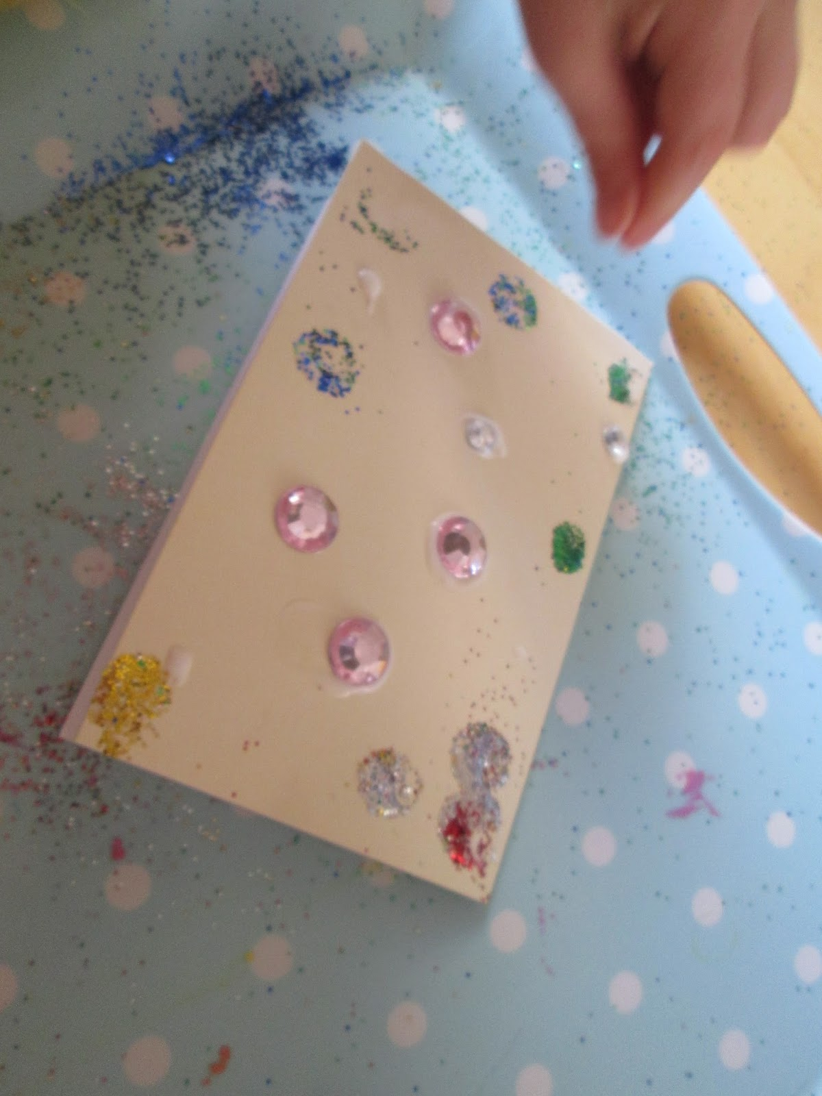 Shaking the glitter over the glue and card