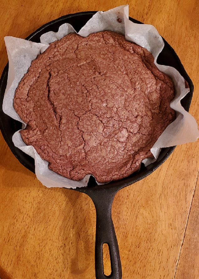 This is a baked chocolate skillet cookie. This is a cookie baked and is cooling in a 10 inch cast iron skillet lined with parchment paper and resting on a oak table