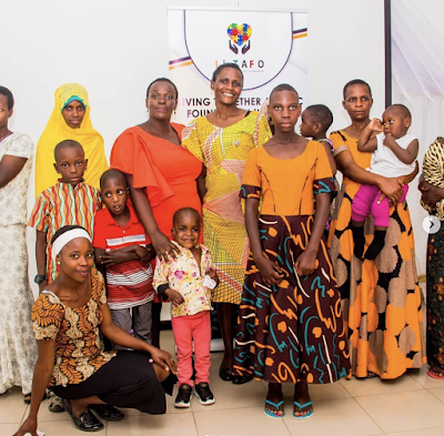 Photo of a group of Tanzanian adults and children, in front of a LI-TAFO banner.